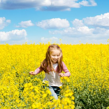 Little girl running through a meadow of yellow flowers bug free.